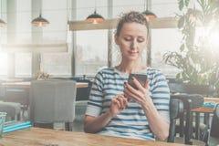 Front View Junge Frau in gestreifter Bluse sitzt im Café bei Tisch und benutzt den Smartphone und liest eBook Stockfoto