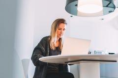 Front View Junge Geschäftsfrau mit dem langen Haar sitzt am weißen Rundtisch und arbeitet auf Laptop Stockbilder