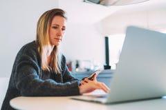 Front View Junge Geschäftsfrau mit dem langen Haar sitzt am weißen Rundtisch und arbeitet auf Laptop Blogging Hippie-Mädchen Stockbild