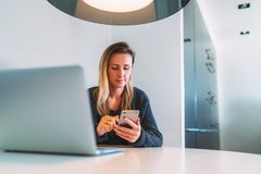 Front View Junge Geschäftsfrau mit dem langen Haar sitzt am weißen Rundtisch, unter Verwendung des Smartphone Auf Tabelle ist Lap Stockbild