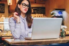 Front View Junge Geschäftsfrau sitzt im Café, das auf Laptop arbeitet Mädchen, das, online lernend blogging ist und überprüfen E- Lizenzfreie Stockfotografie
