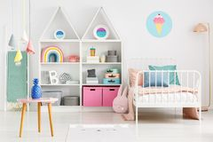 Front view of a kid`s room interior with a table, shelves with b. Oxes and rainbow, single bed and ice-cream poster on the wall Stock Photos