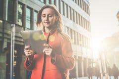 Front View La donna attraente sorridente dei giovani in cappotto arancio sta stando sulla via della città ed utilizza il computer Immagini Stock