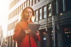Front View La donna attraente sorridente dei giovani in cappotto arancio sta stando sulla via della città ed utilizza il computer Fotografie Stock Libere da Diritti