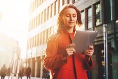 Front View La donna attraente sorridente dei giovani in cappotto arancio sta stando sulla via della città ed utilizza il computer Immagini Stock Libere da Diritti