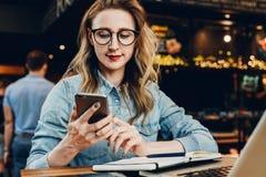 Front View La empresaria joven se está sentando en cafetería en la tabla delante del ordenador y del cuaderno, usando smartphone imagen de archivo libre de regalías