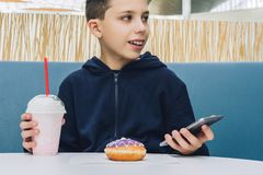 Teenager boy sits at table in cafe, drinks milkshake, eats donut, holds smartphone in his hand. Boy plays mobile games. Front view. Laughing teenager boy sits Royalty Free Stock Images