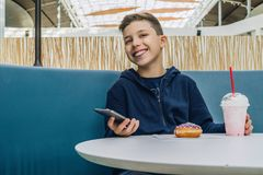 Teenager boy sits at table in cafe, drinks milkshake, eats donut, holds smartphone in his hand. Boy plays mobile games. Front view. Laughing teenager boy sits Stock Images
