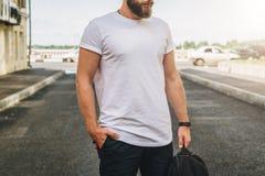 Front View Le jeune homme millénaire barbu habillé dans le T-shirt blanc est des supports sur la rue de ville Voir les mes autres photos stock