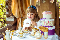 Front view of an little beautiful girl holding a piece of cake on a spoon at the table. Front view of an little beautiful girl in the scenery of Alice in Stock Photo