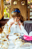 Front view of an little beautiful girl in the scenery of Alice in Wonderland drinking a tea at the table in the park Stock Photography