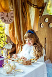 Front view of an little beautiful girl in the scenery of Alice in Wonderland holding a cup of tea at the table Stock Photography