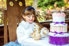 Front view of an little beautiful girl in the scenery of Alice in Wonderland holding a cup of tea at the table Royalty Free Stock Photo