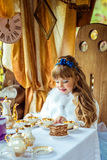 Front view of an little beautiful girl in the scenery of Alice in Wonderland holding a cup of tea at the table Royalty Free Stock Image