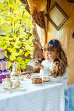 Front view of an little beautiful girl in the scenery of Alice in Wonderland holding a cup of tea at the table. In the autumn park stock photo