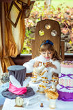 Front view of an little beautiful girl in the scenery of Alice in Wonderland pouring tea into a cup at the table Royalty Free Stock Photos
