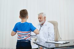 Doctor examining little boy with stethoscope. Front view of little boy during consultation in hospital. Serious doctor sitting working providing medical royalty free stock photos
