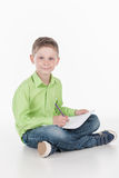 Front view of little boy siting on floor. stock photography