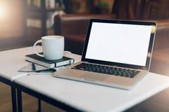 Front View Lugar de trabajo vacío En la mesa de centro blanca es el ordenador portátil con la pantalla en blanco, taza de café, c Fotografía de archivo