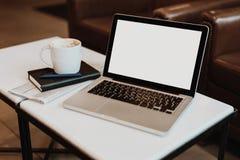 Front View Lugar de trabajo vacío En la mesa de centro blanca es el ordenador portátil con la pantalla en blanco, taza de café, c Foto de archivo libre de regalías
