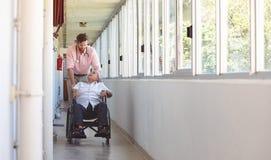 Male doctor pushing senior wheelchair man stock photo