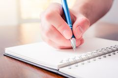 Front View Of A Male Hand Writing With A Pen In A Blank Book In Front Of A Bright Background. The Front View Of A Male Hand Writing With A Pen In A Blank Book In Royalty Free Stock Images