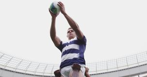 Male rugby players playing rugby match in stadium 4k. Front view of male rugby players playing rugby match in stadium. They are passing rugby ball 4k stock footage