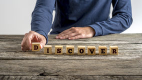 Front view of a man assembling word Discover with wooden cubes Stock Photos