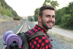 Front view of man with backpack hiking in forest.  Royalty Free Stock Images