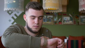 Front view of man checking messages on smartwatch while he is sitting in a pub stock footage