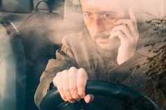 Front view of man driving car and talking on mobile stock photography