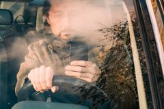 Front view of man driving car and texting on mobile royalty free stock photo