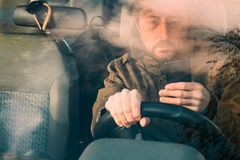 Front view of man driving car and texting on mobile royalty free stock photos