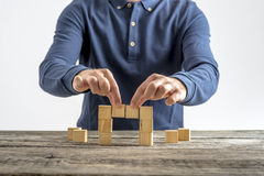 Front view of a man making a bridge with wooden cubes Stock Images