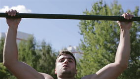 Front view. Man with naked chest is pulling up outdoors. The blue sky and green trees on the background. Sport athlete chin-ups stock footage