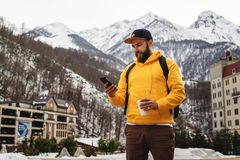 Front view. Man tourist in yellow hoodie, cap with backpack stands on background of high snowy mountains and using smartphone. Front view. Bearded male tourist royalty free stock photos