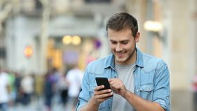 Man walking and using a smart phone in the street stock footage