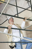 Front view of mature man climbing scaffold Stock Photography