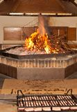 Fire in fireplace and preparation to grill duck breasts. Front view, medium distance of fire in fireplace, using dried grape fines and preparation to grill duck royalty free stock photo