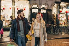 Couple Christmas Shopping. Front view of a Mid adult couple walking around a city street after christmas shopping stock image