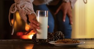Woman at home at Christmas time. Front view mid section of a mixed race woman in her sitting room at Christmas putting a glass of milk down on a coffee table stock footage