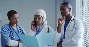 Front view of Middle-East female doctor talking on mobile phone with her colleagues in hospital stock video