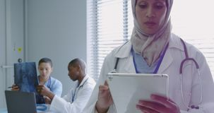Front view of middle-east female doctor using digital tablet in hospital stock video footage