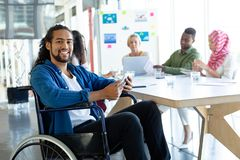 Disabled businessman with digital tablet looking at camera in conference room during meeting. Front view of Mixed-race disabled businessman with digital tablet royalty free stock image