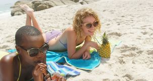 Front view of mixed-race female friends drinking cocktail drinks on the beach 4k. Front view of mixed-race female friends drinking cocktail drinks on the beach stock video footage
