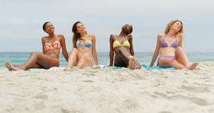 Front view of mixed-race female friends relaxing with eyes closed on the beach 4k. Front view of mixed-race female friends relaxing with eyes closed on the beach stock video