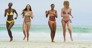 Front view of mixed-race female friends running on the beach 4k. Front view of mixed-race female friends running on the beach. They are having fun 4k stock footage