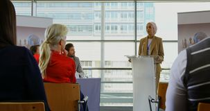 Female speaker speaking in a business seminar 4k. Front view of a mixed-race female speaker speaking to the public and standing on the podium in a business stock footage