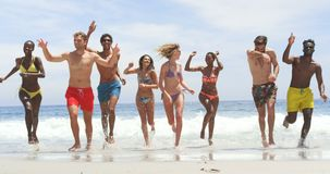 Front view of mixed-race friends running together on the beach 4k. Front view of mixed-race friends running together on the beach. They are having fun 4k stock footage