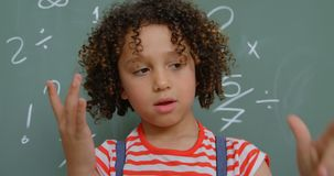 Front view of mixed-race schoolgirl counting with her finger against chalkboard in classroom 4k. Front view of mixed-race schoolgirl counting with her finger stock video footage